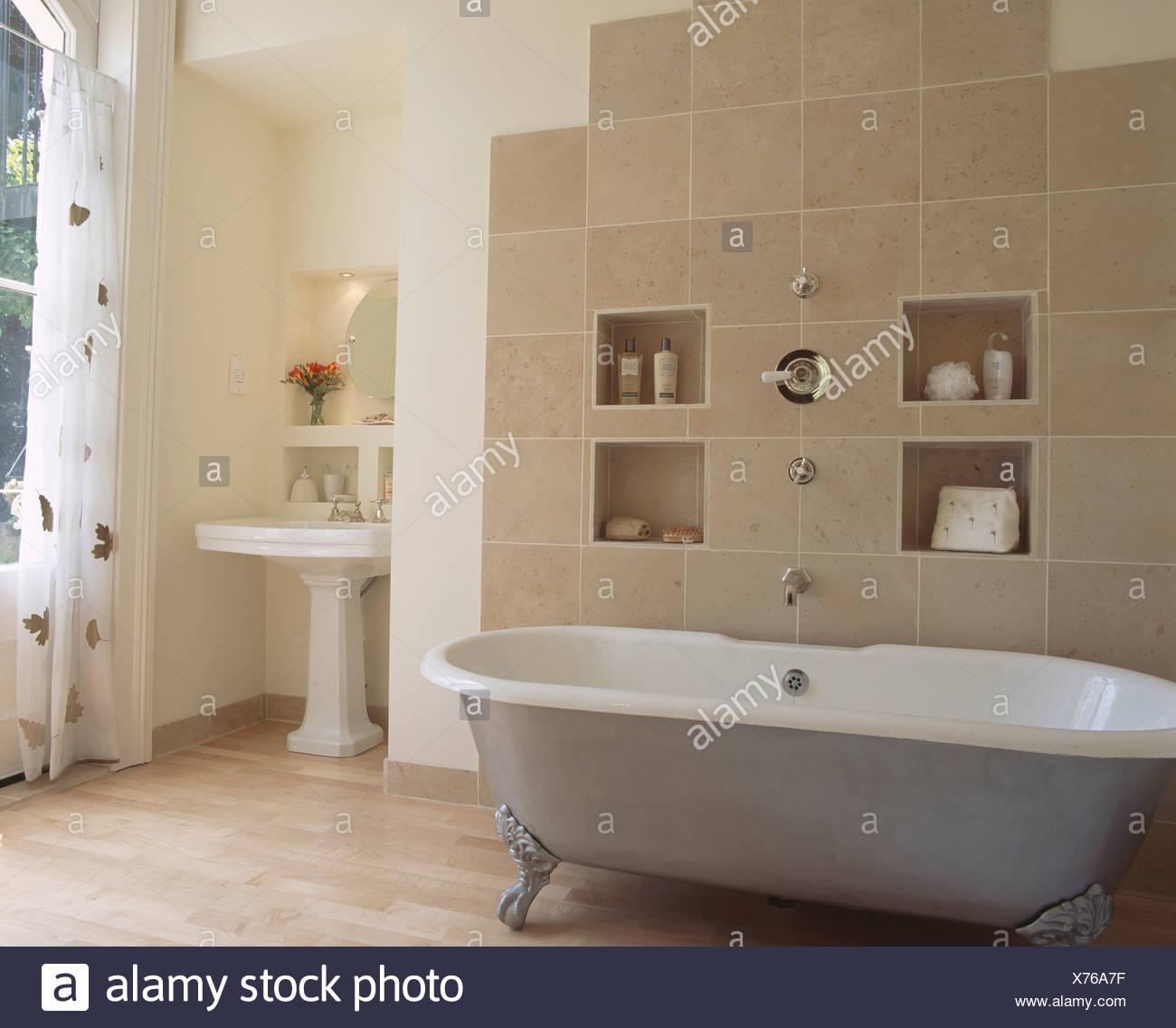 Alcove shelving on beige tiled wall behind metallic clawfoot bath in ...