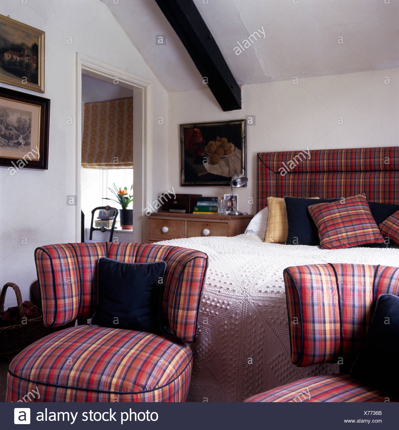 Red Plaid Upholstered Chairs At The Foot Of Bed With A Cream Crocheted  Bedspread In White Attic Bedroom