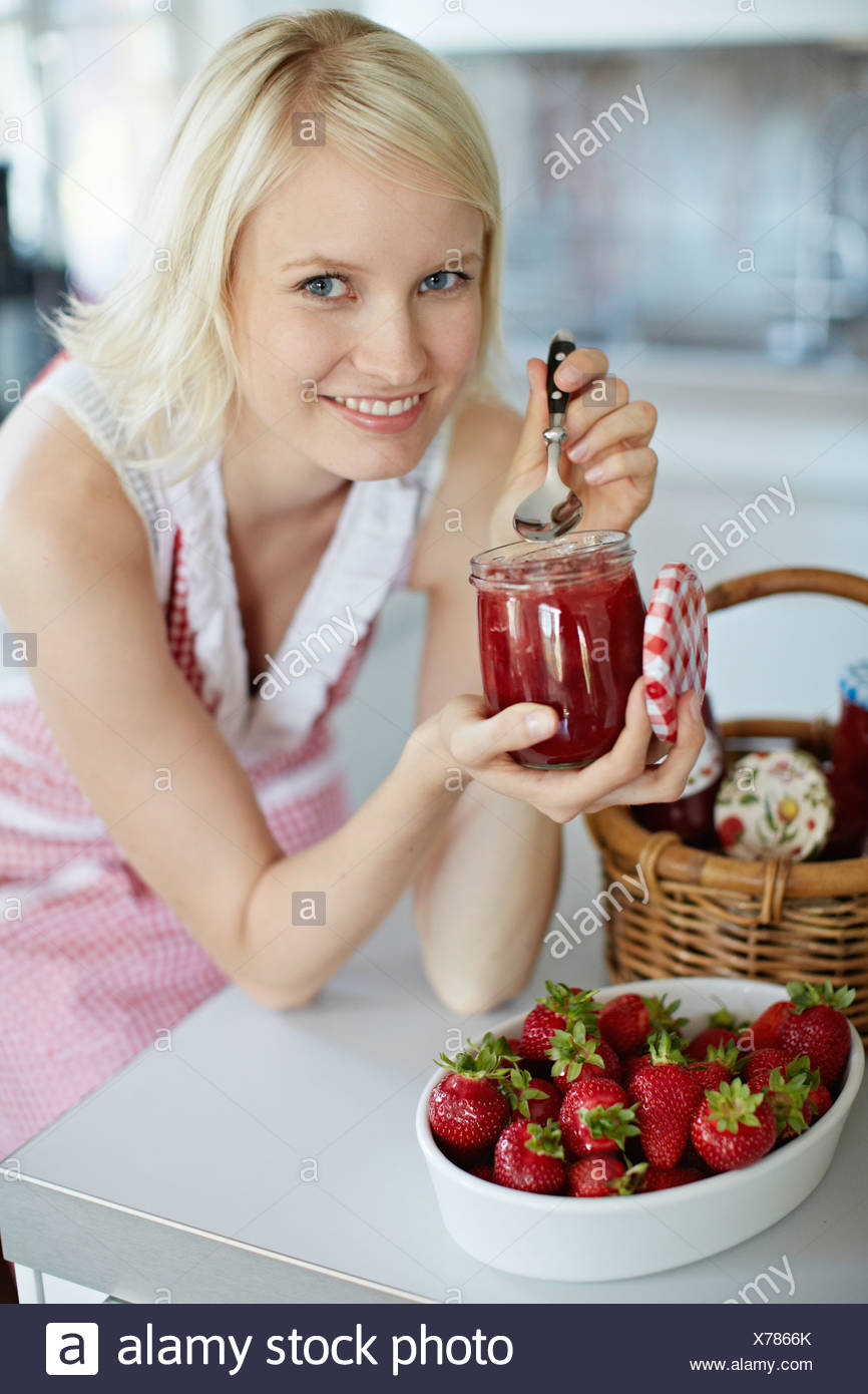 Woman eating jelly from jar in kitchen - Stock Image