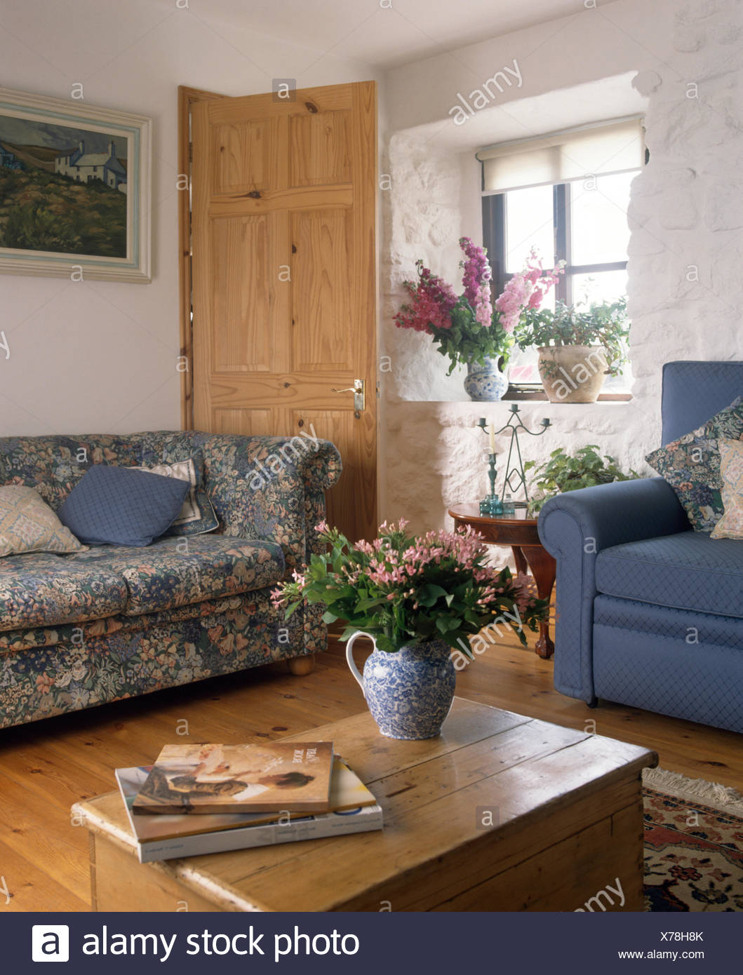 Old Pine Chest And Blue Patterned Chesterfield Sofa With A Blue Armchair In  A Nineties Cottage Living Room With