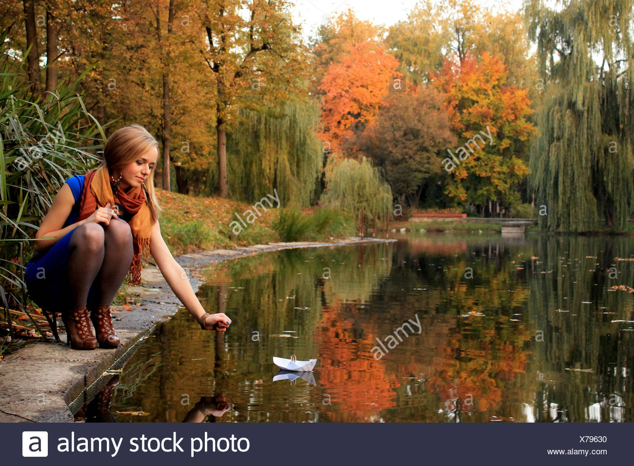 Young woman with paper ship in park - Stock Image