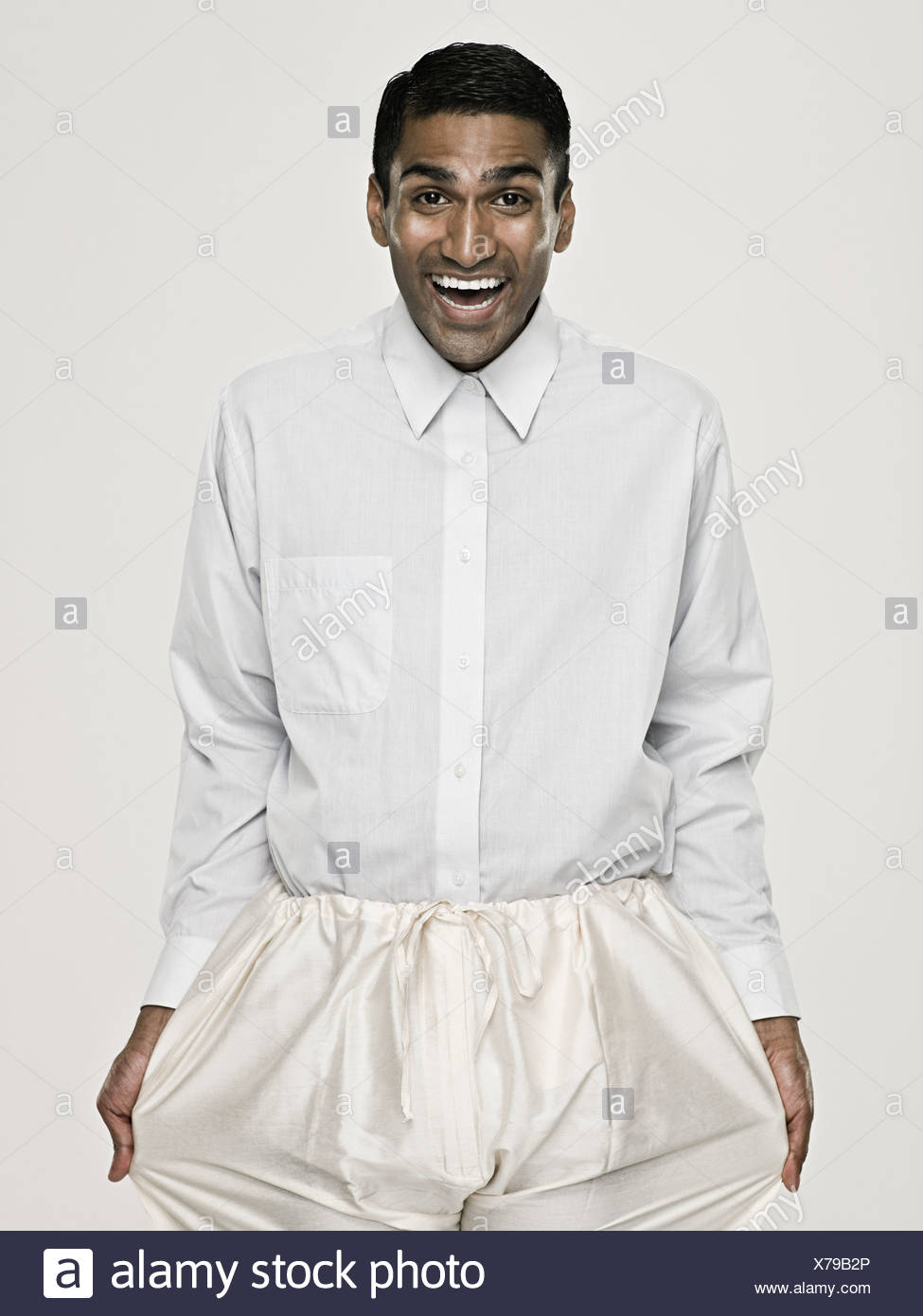 Asian man pulling his trousers - Stock Image