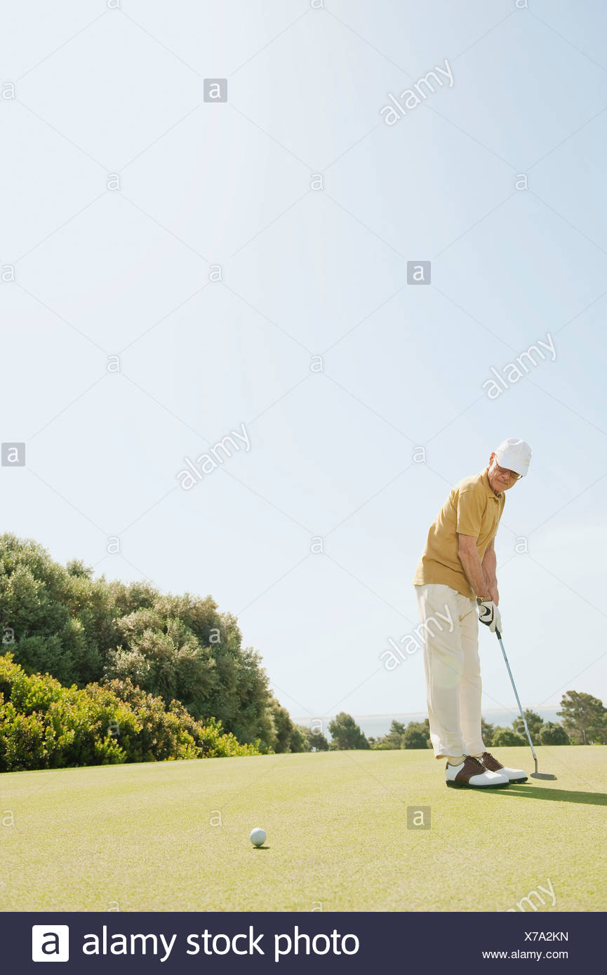 Spain, Mallorca, Senior man playing golf, side view - Stock Image