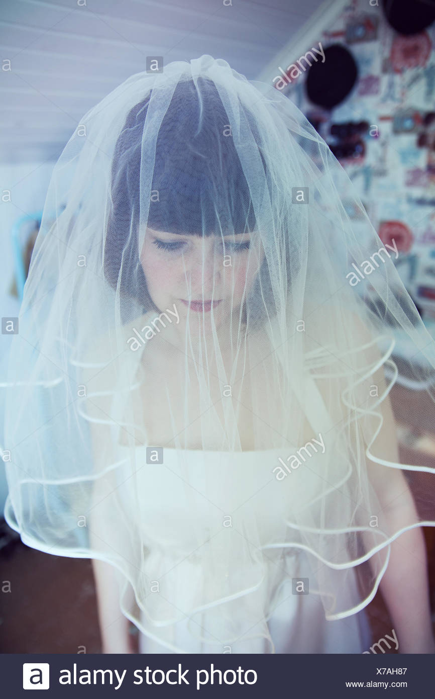 Sad young woman in wedding veil, gazing down - Stock Image