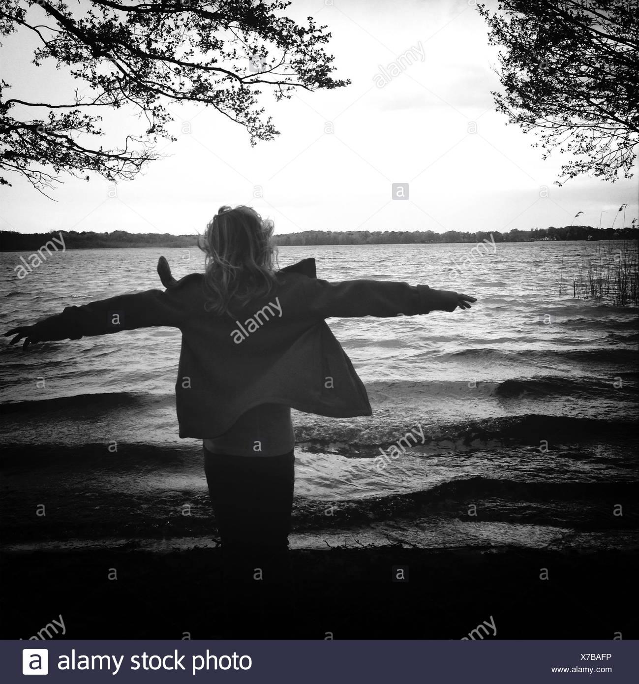 Rear View Of Woman Enjoying Wind At Shore - Stock Image