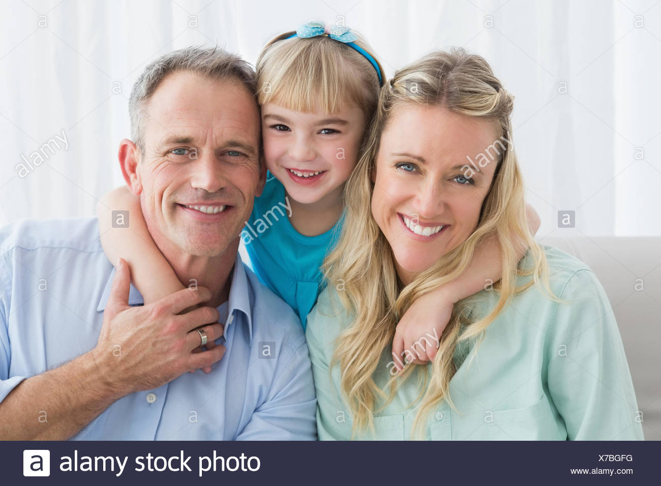 Happy family relaxing on the couch - Stock Image