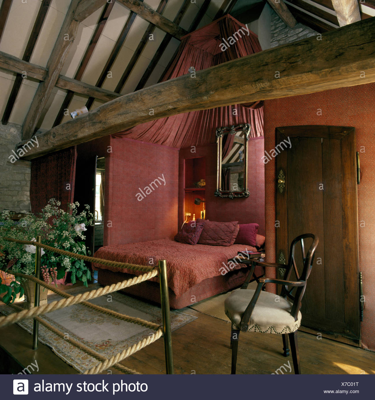 Pink Fabric On Walls In Open Plan Bedroom In Nineties Barn Conversion With  Rustic Wooden Beams On Ceiling