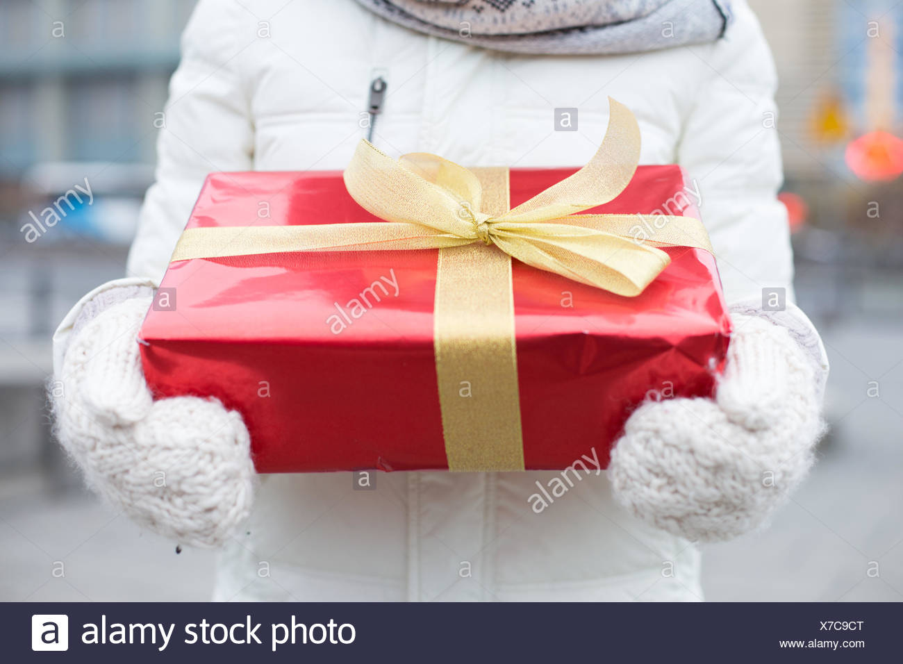 Midsection of woman holding gift box winter - Stock Image