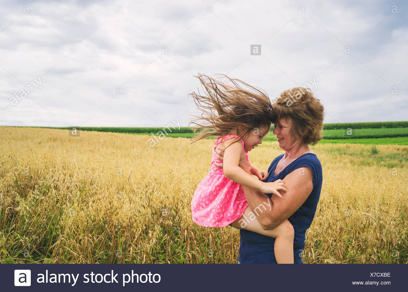 Mature women lifting up baby girl - Stock Image