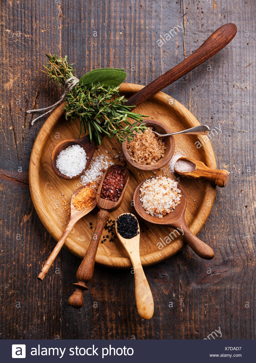 Different types of food coarse Salt in wooden spoons on dark background - Stock Image