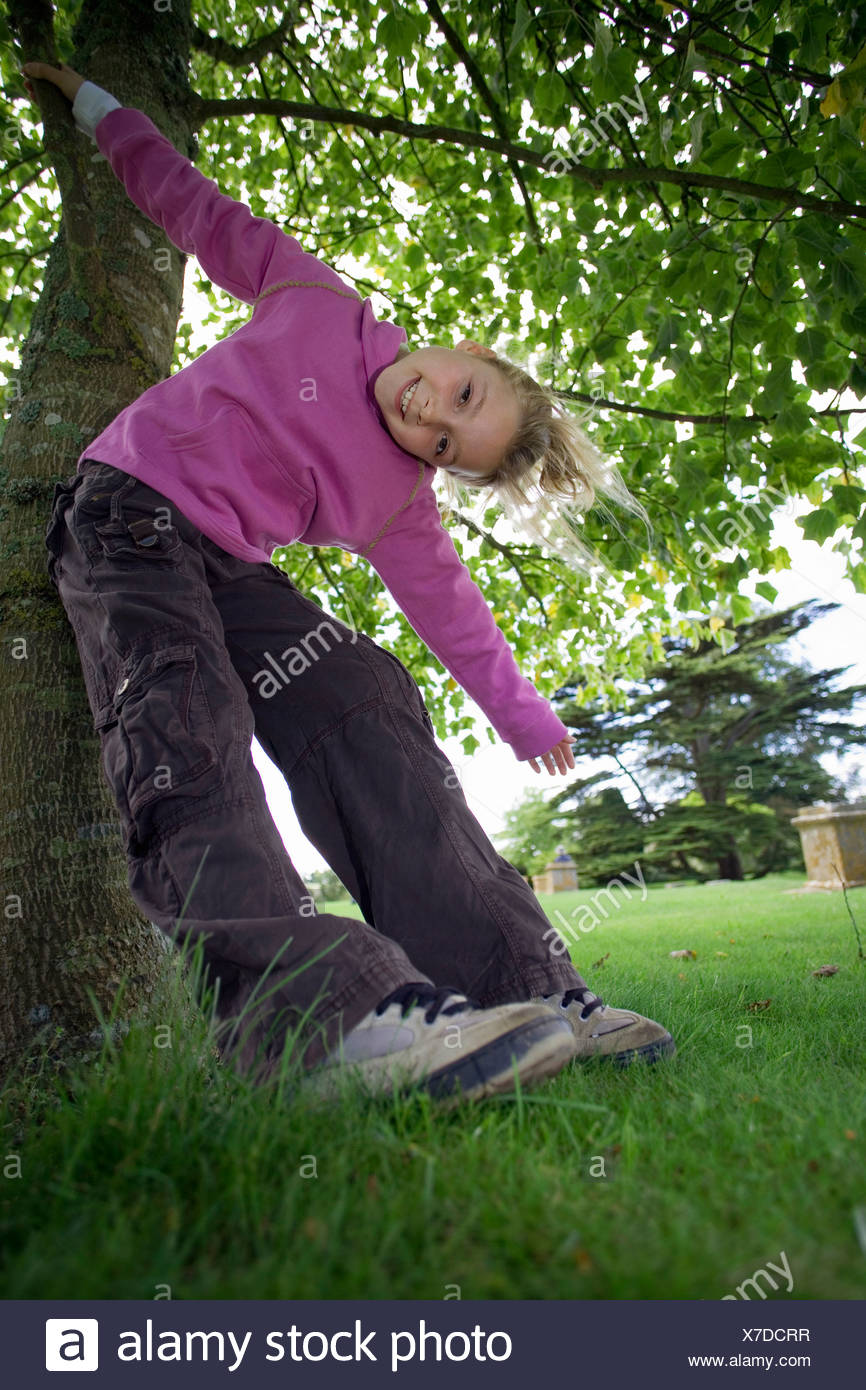 Girl 7 9 wearing purple top and combat trousers swinging from branch in garden arms outstretched head cocked smiling portrait - Stock Image