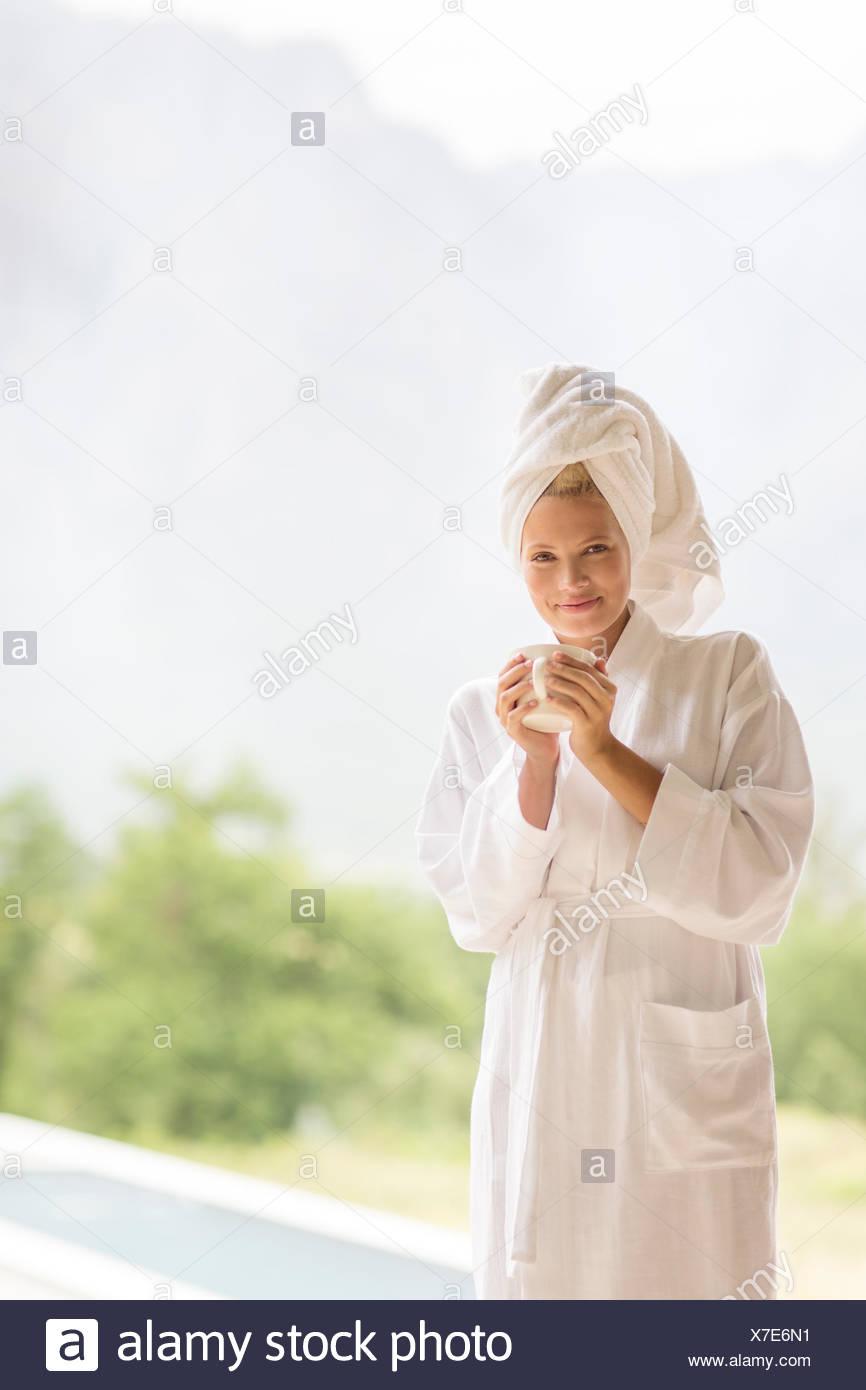 Woman in bathrobe having coffee outdoors - Stock Image