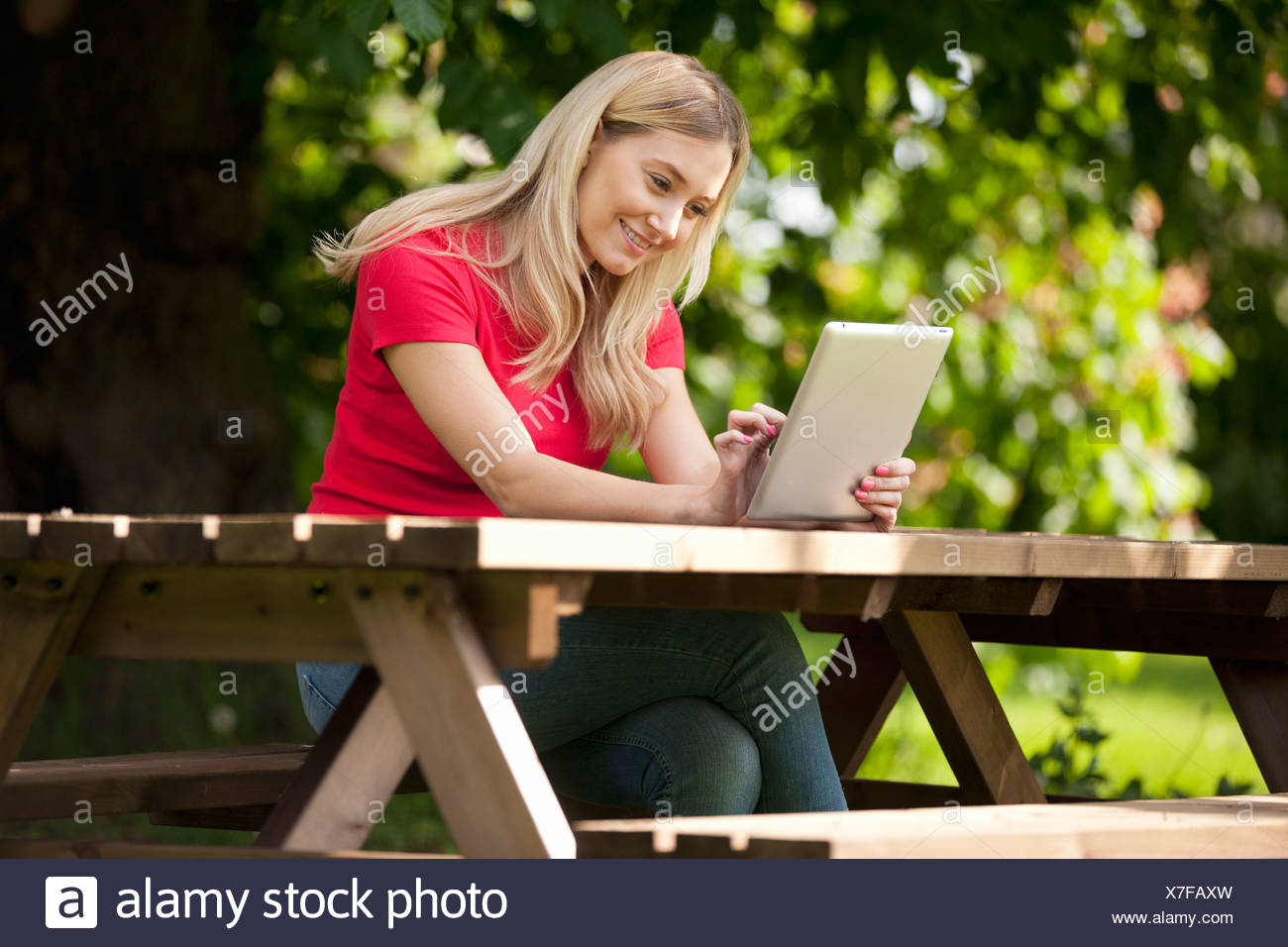 A young woman sitting at a bench using a digital tablet, smiling - Stock Image