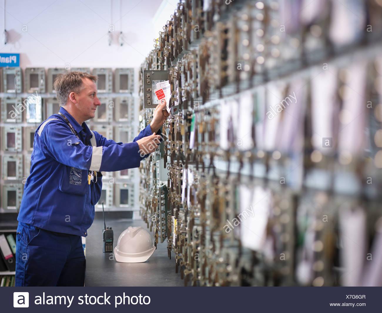 Engineer selecting equipment keys in power station - Stock Image