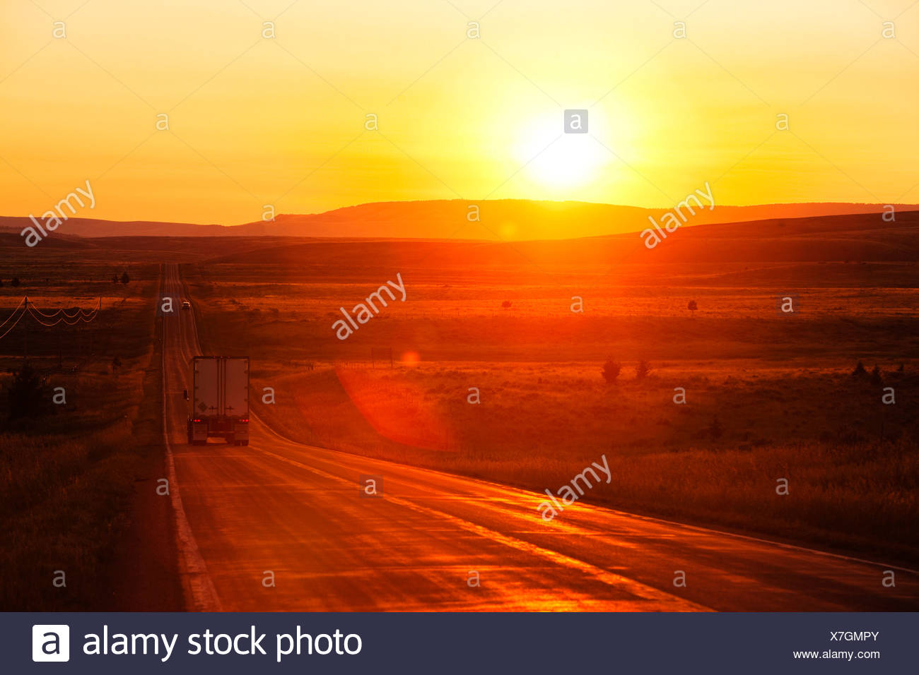 A shipping truck on a long straight highway at sunrise in Montana. - Stock Image