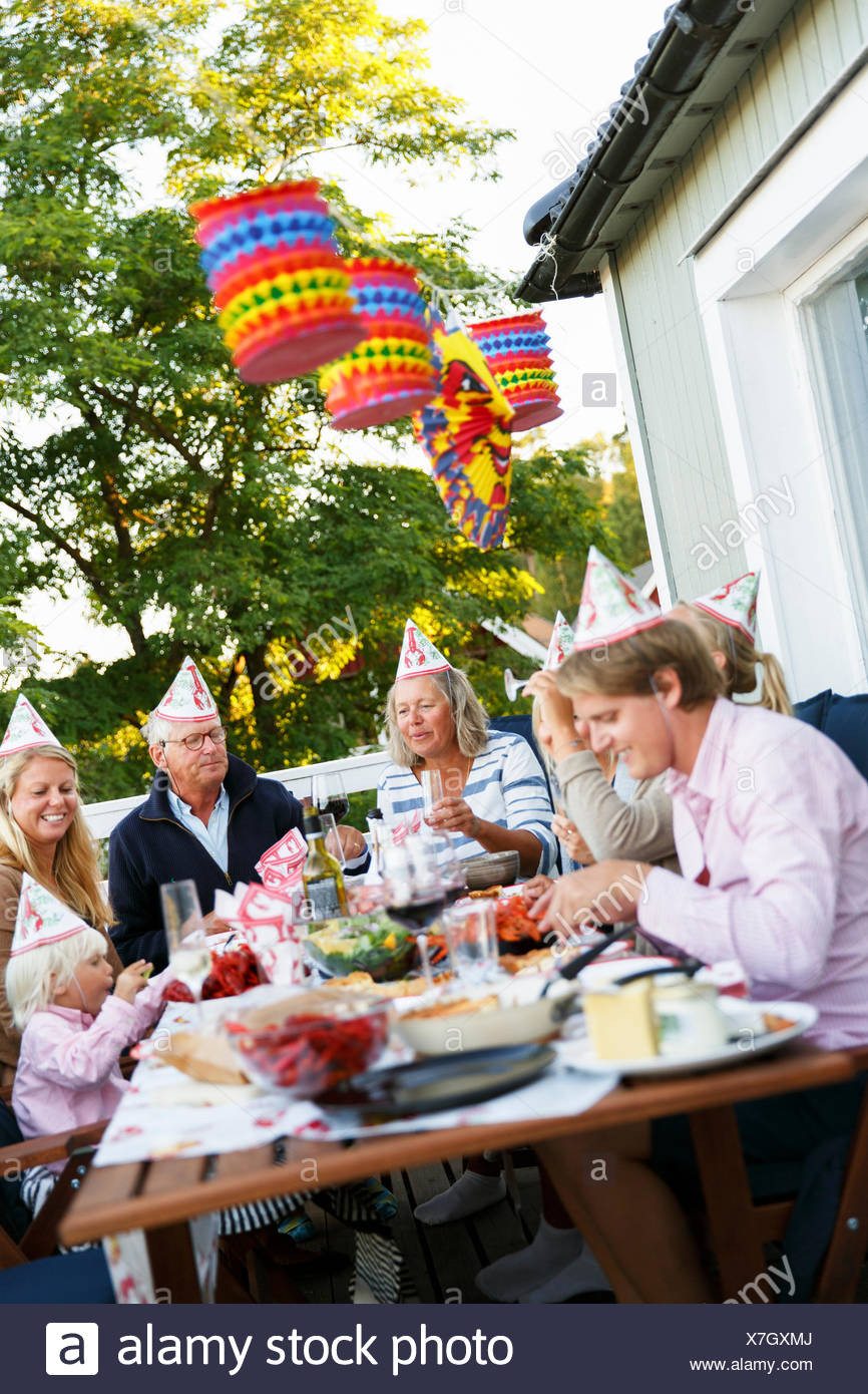 Sweden, Sodermanland, Jarna, Family with small child (2-3) sitting at table celebrating Crayfish Party - Stock Image