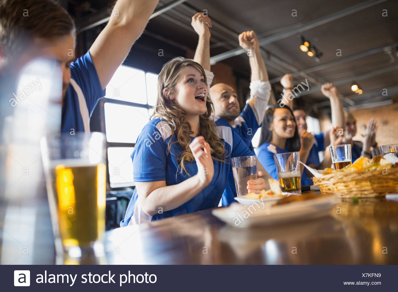 Sports fans cheering at bar in pub - Stock Image