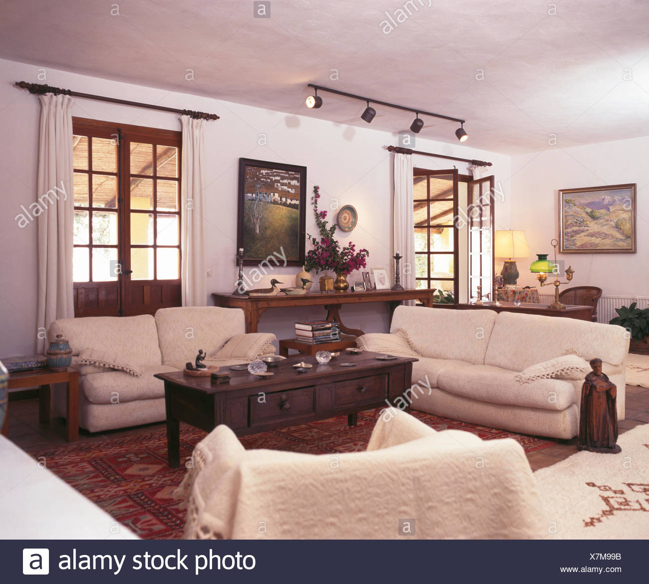 Cream sofas and dark wood coffee table in white Spanish living room ...