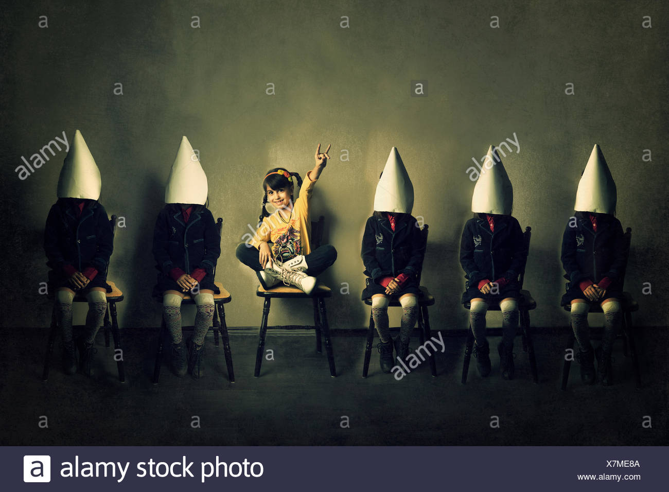 Six girls sitting on chairs in a row - Stock Image