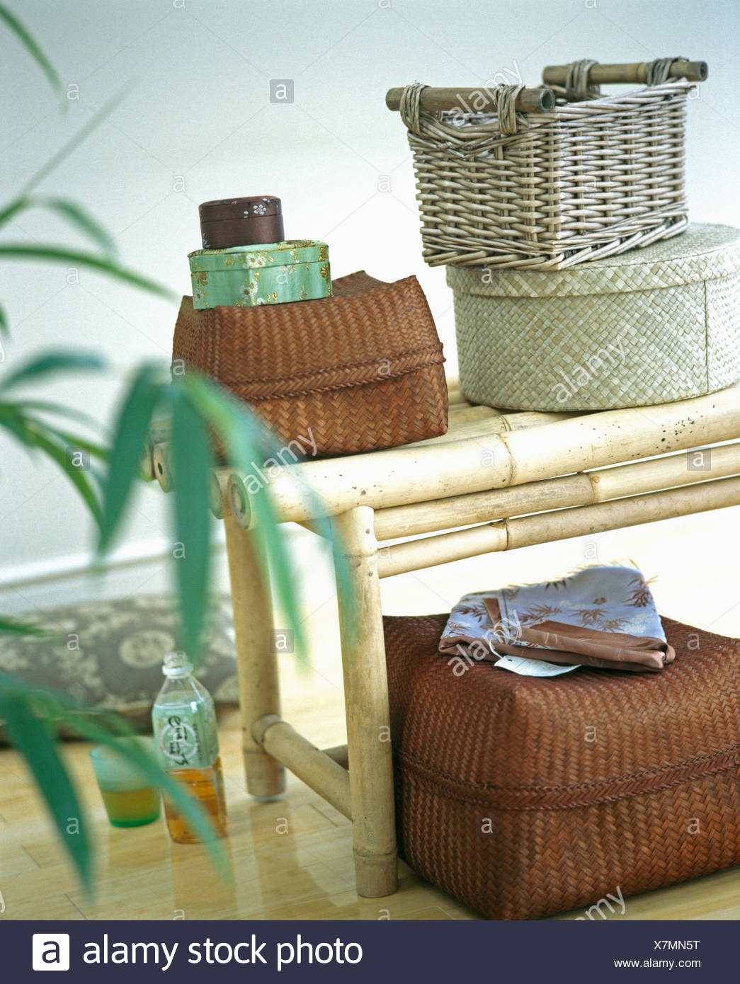 Close Up Of Lidded Wicker And Rattan Storage Boxes On Bamboo Stool