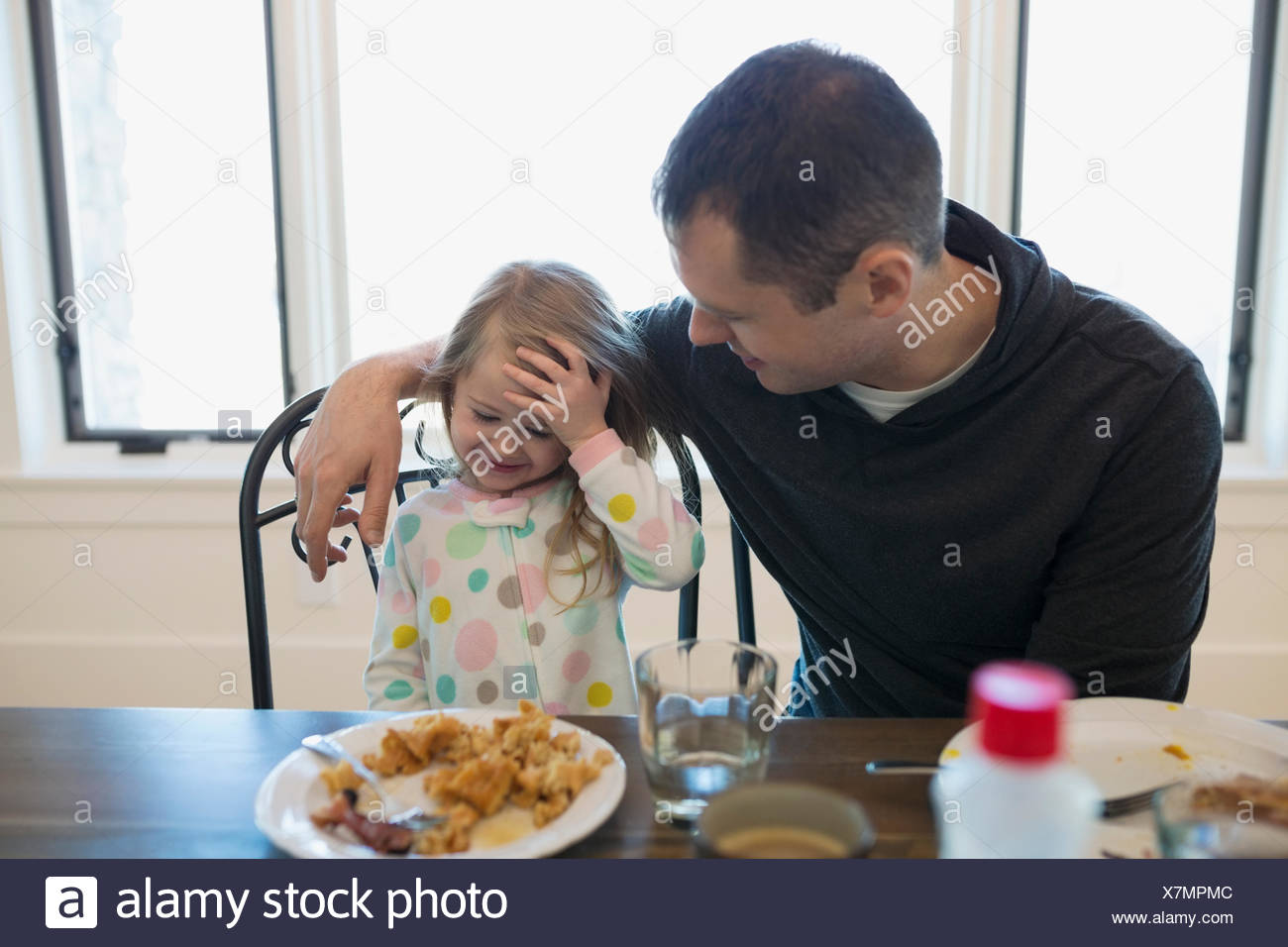 Father and daughter eating waffles at breakfast table - Stock Image