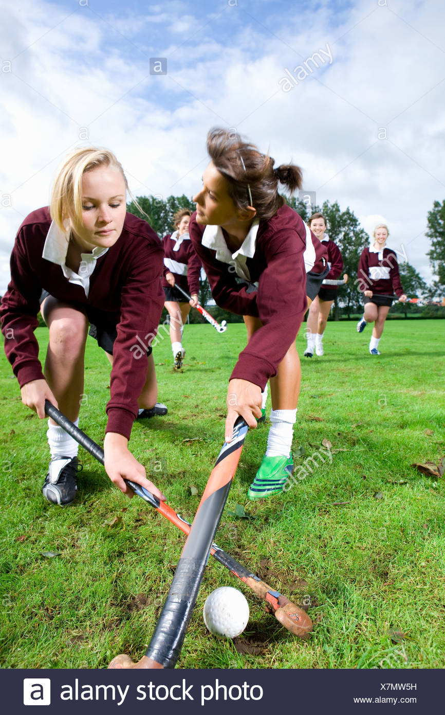 Teenage girls playing field hockey - Stock Image