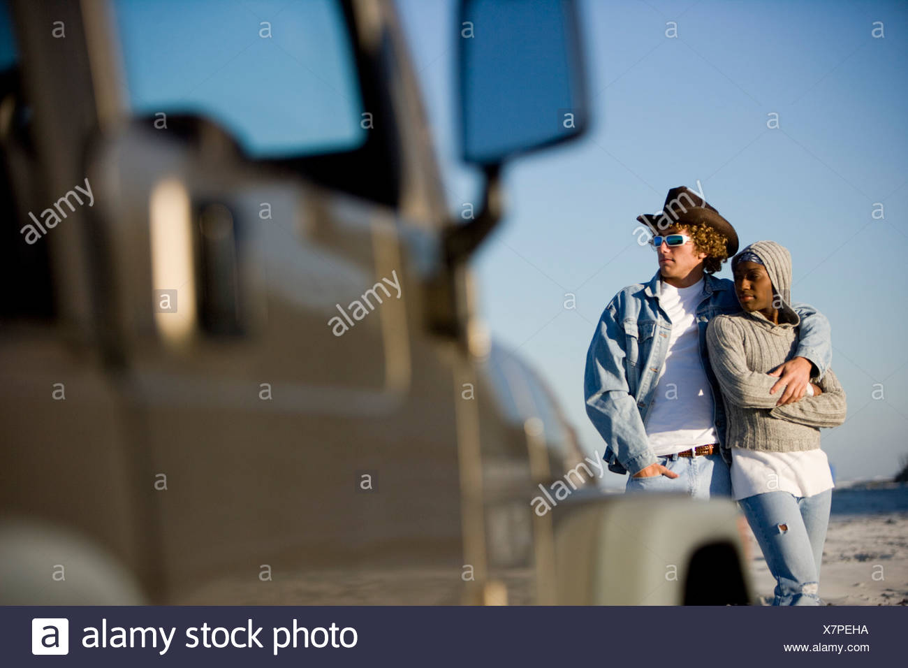 Young interracial couple standing by jeep - Stock Image