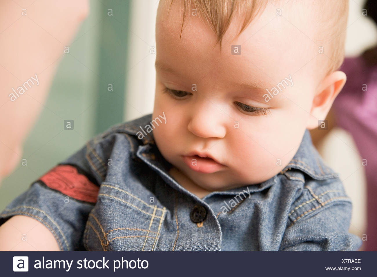 Baby in a denim jacket - Stock Image
