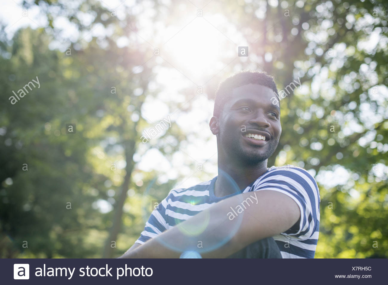 A man in a striped shirt under the shade of trees - Stock Image