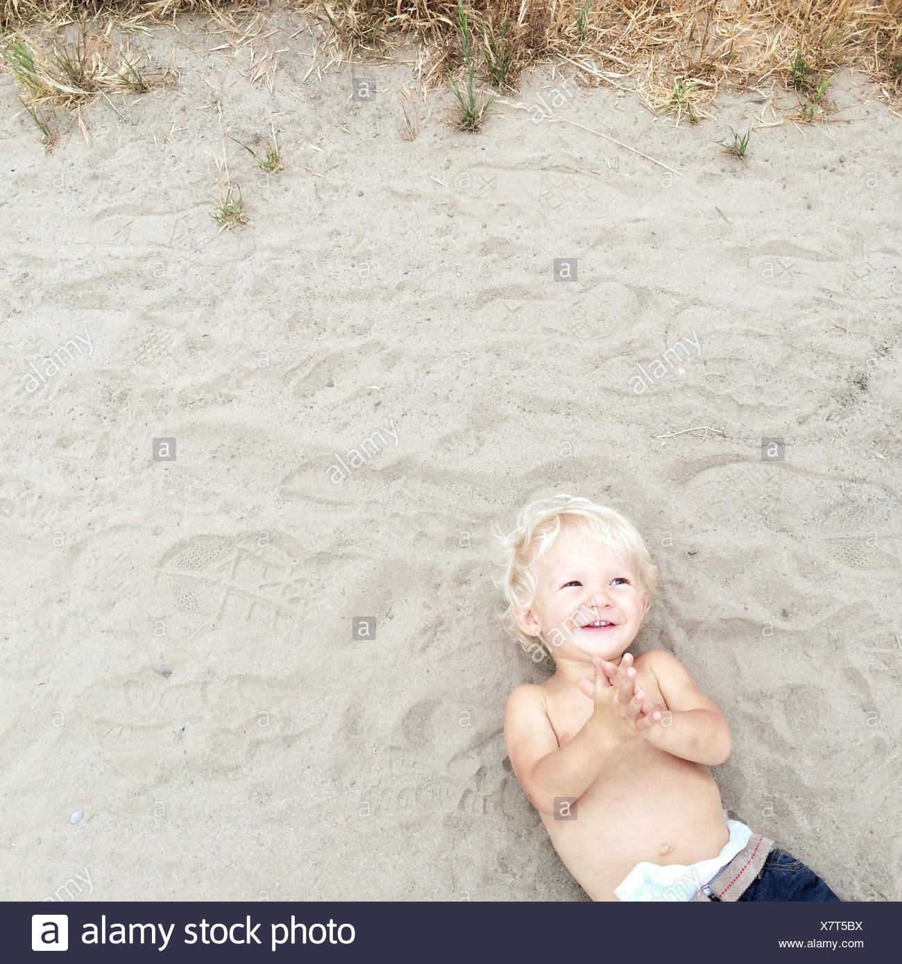 Overhead view of boy lying on beach - Stock Image