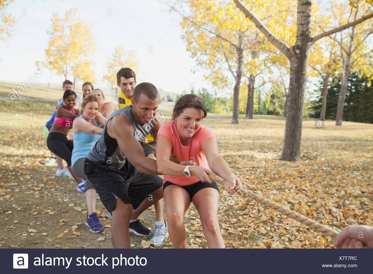 Fitness class doing tug of war outdoors. - Stock Image