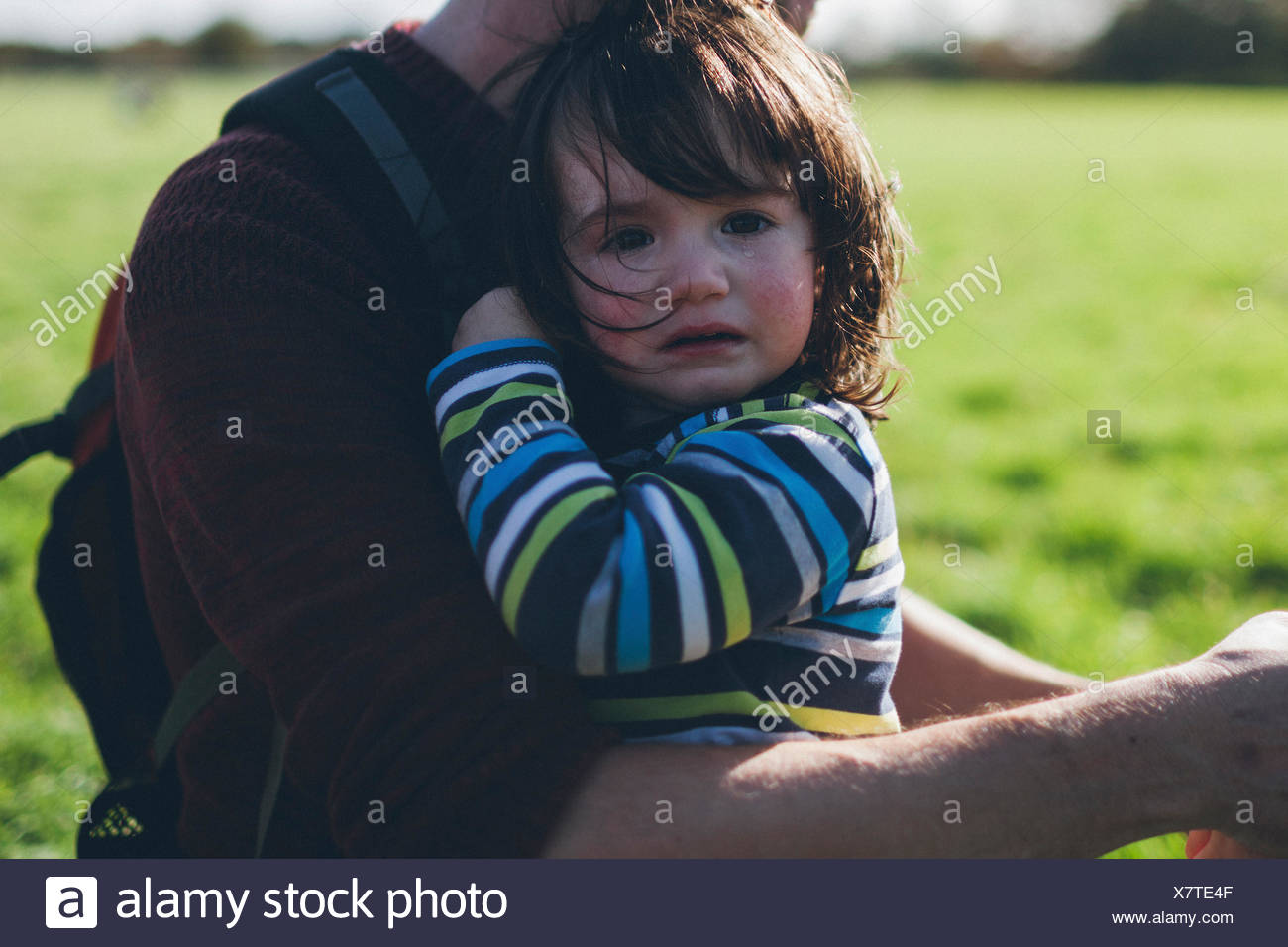 Boy crying in his father's arms - Stock Image