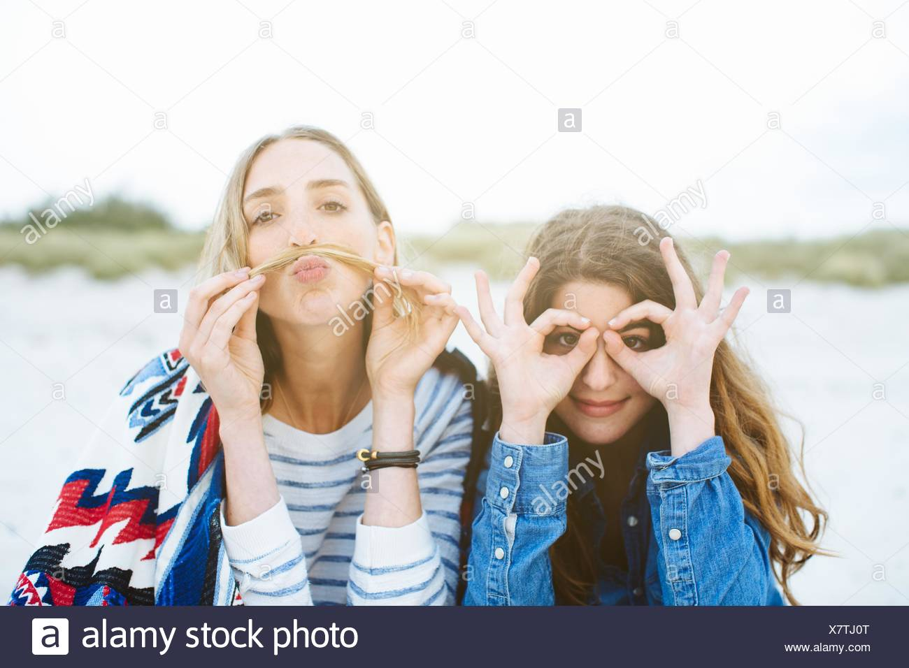 Portrait of two young female friends making moustache and spectacled faces on beach - Stock Image