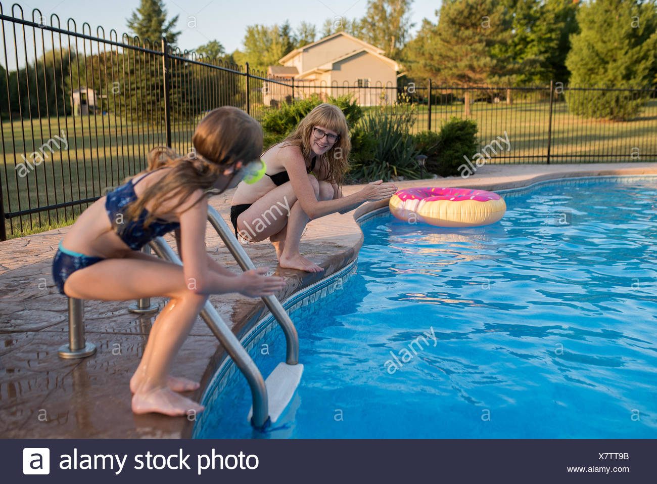 Mother And Daughter On Edge Of Swimming Pool, Ready To Dive In   Stock Image