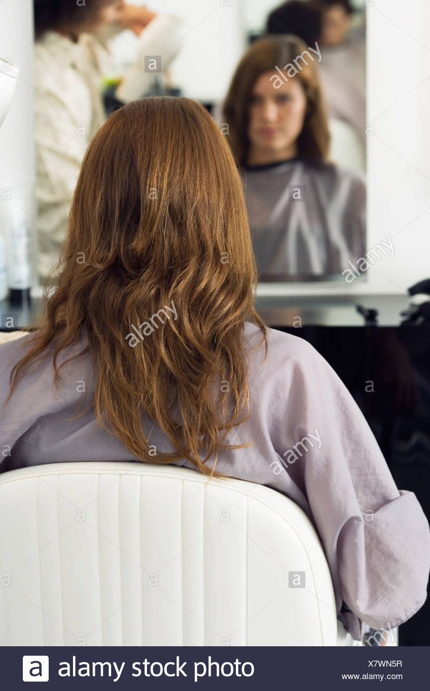 Hairdresser Blow Drying Woman S Hair With Hair Dryer In Salon Rear
