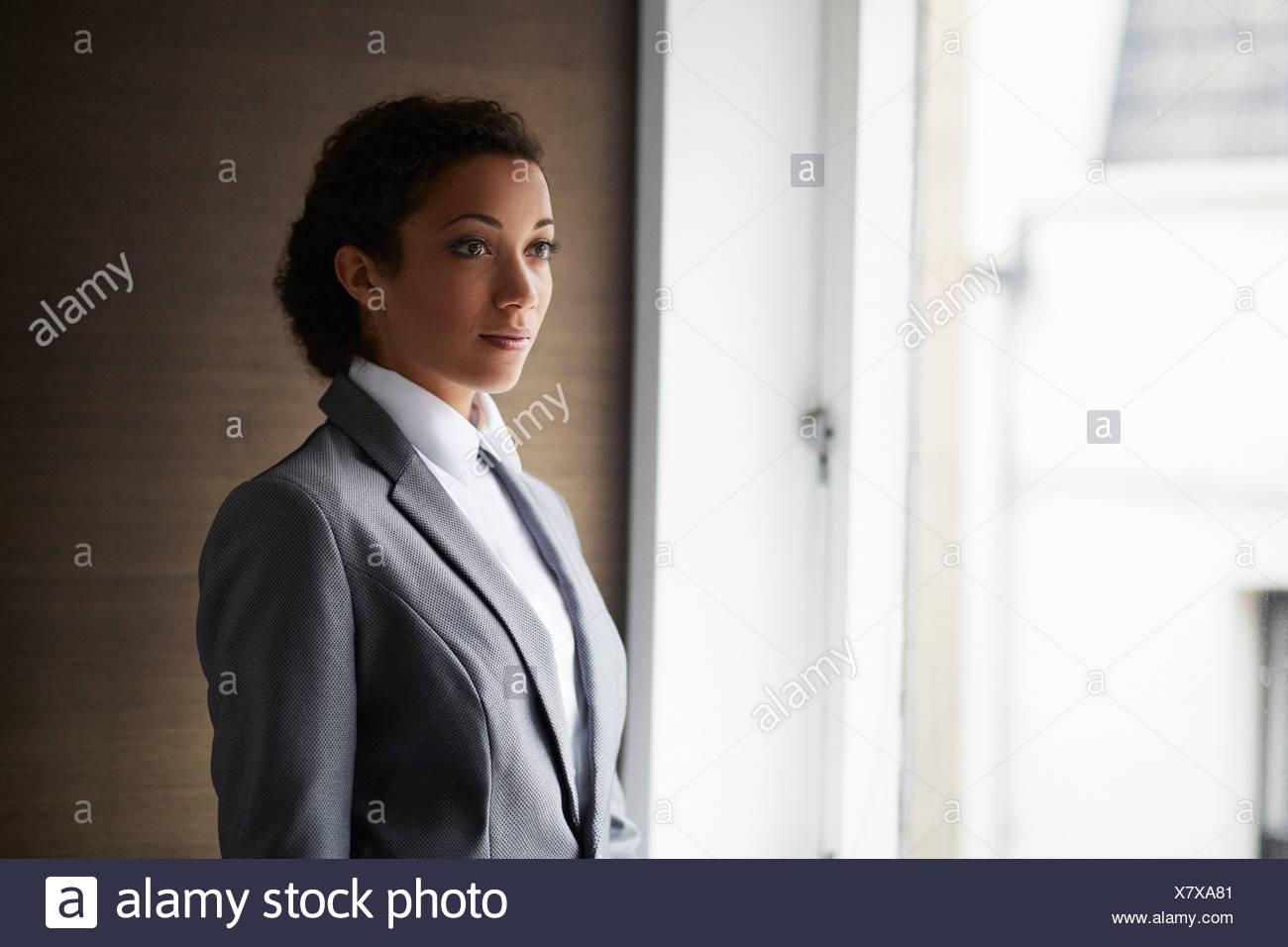 Portrait of businesswoman by window - Stock Image