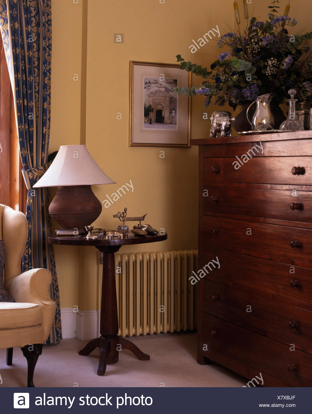 Earthenware Lamp On Antique Side Table In Corner A Traditional Living Room  With A Vintage Chest Of Drawers