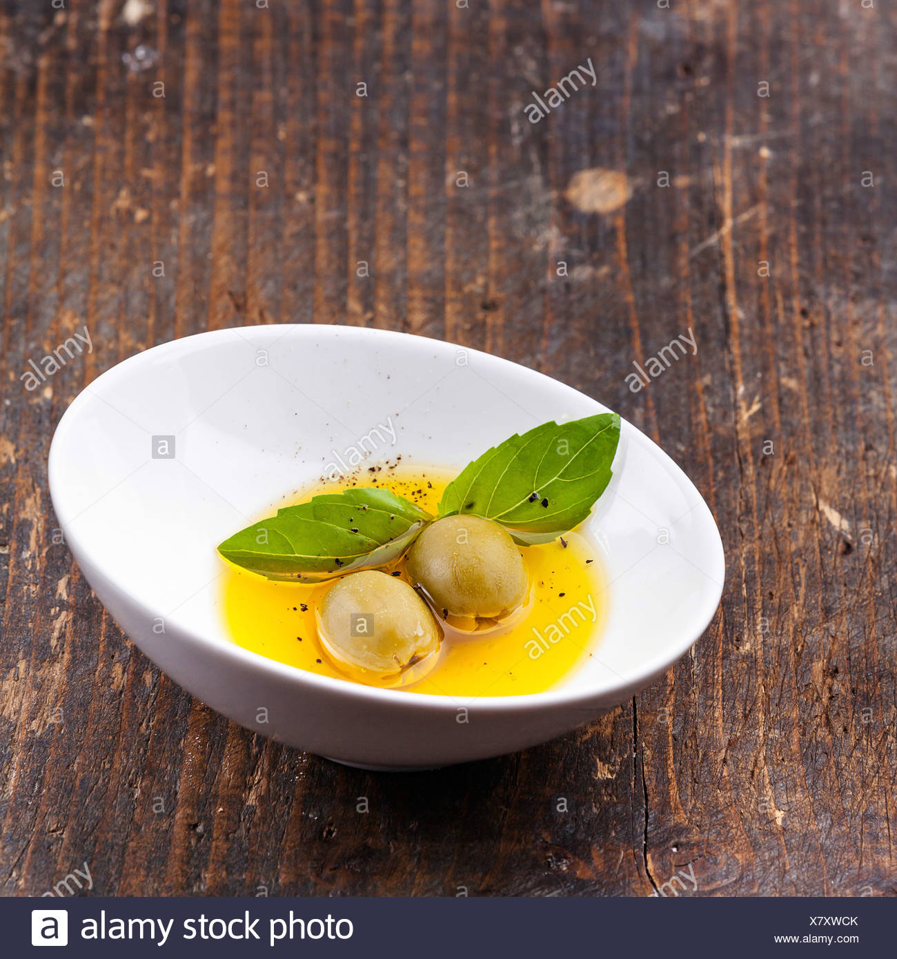 Olives and olive oil in bowl - Stock Image