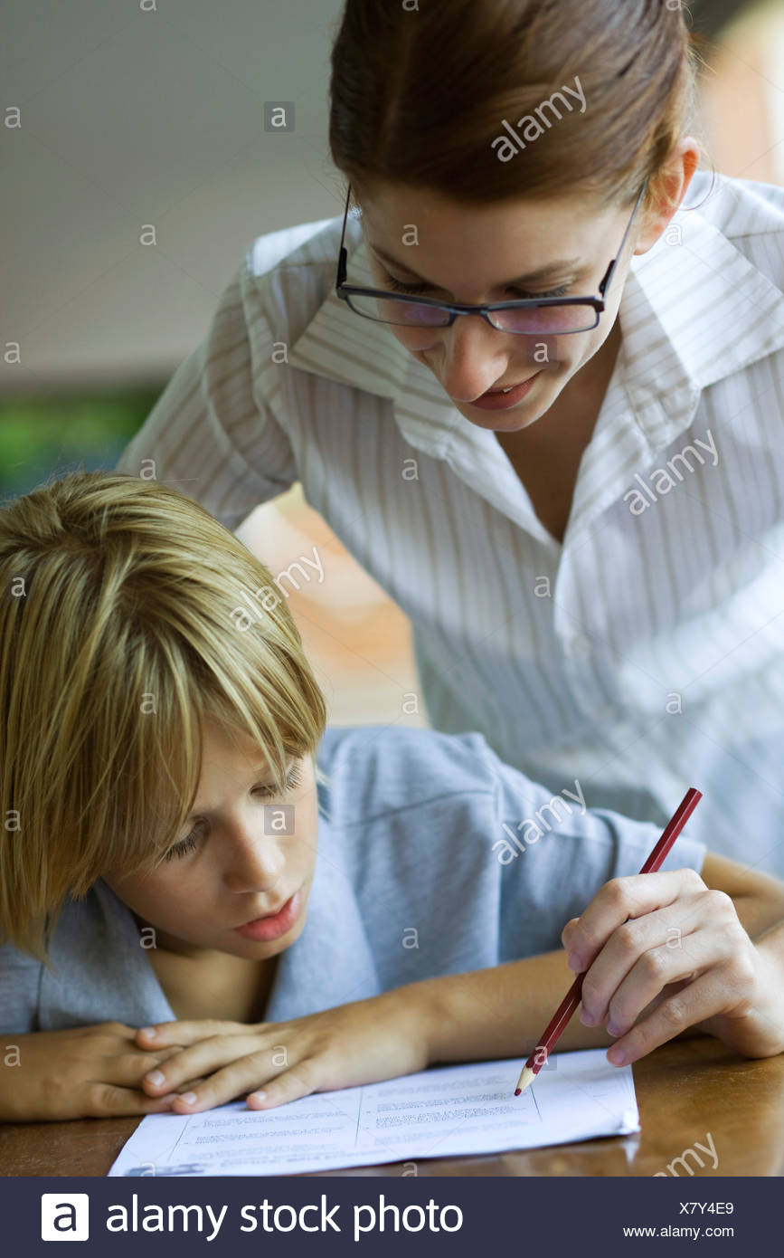 Junior high student watching at teacher corrects classwork - Stock Image
