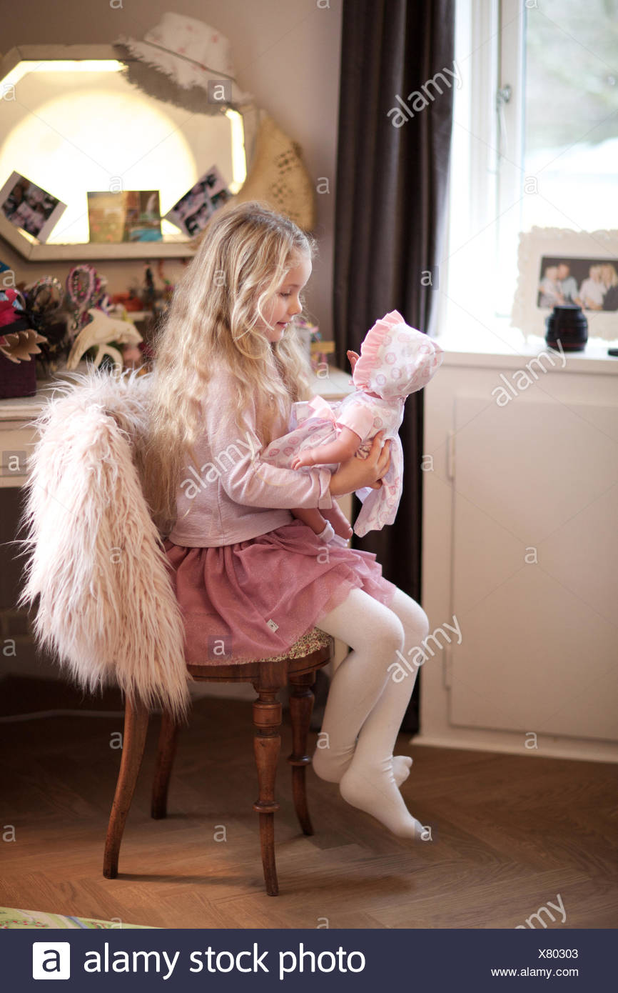 girl playing with her baby doll. day care, kid, playroom, pretend game. - Stock Image