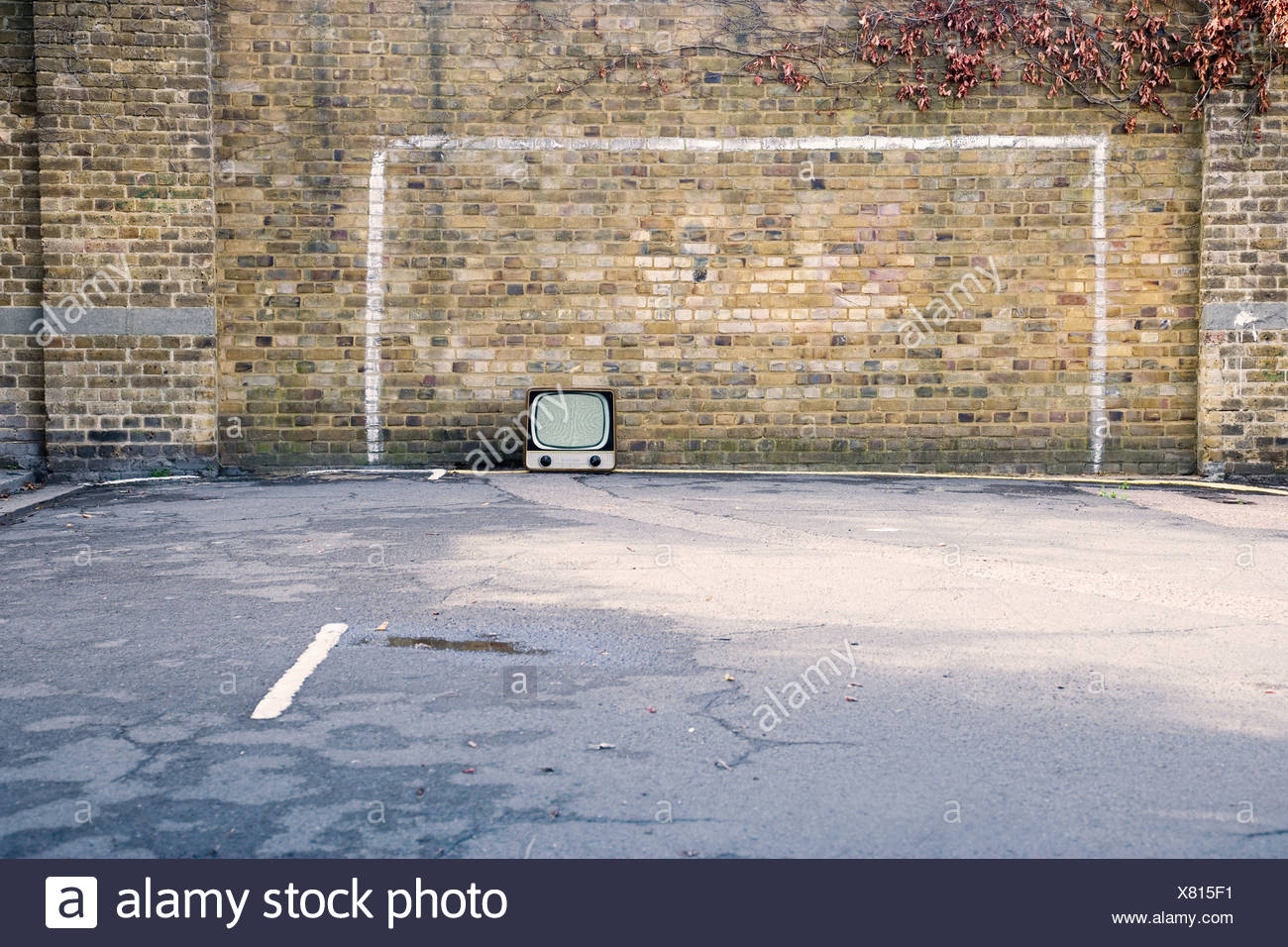Retro television in football goal painted on brick wall - Stock Image