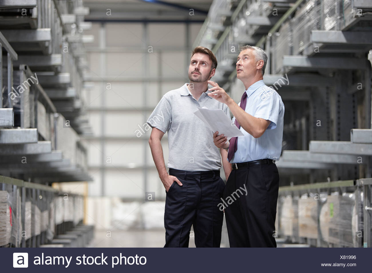 Worker and manager checking products in engineering warehouse - Stock Image