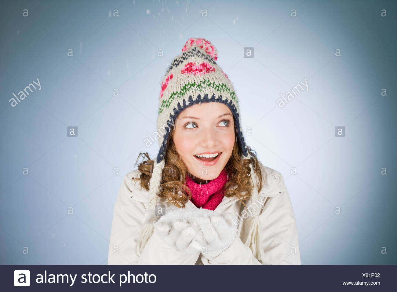 A young woman holding a handful of snow, laughing - Stock Image