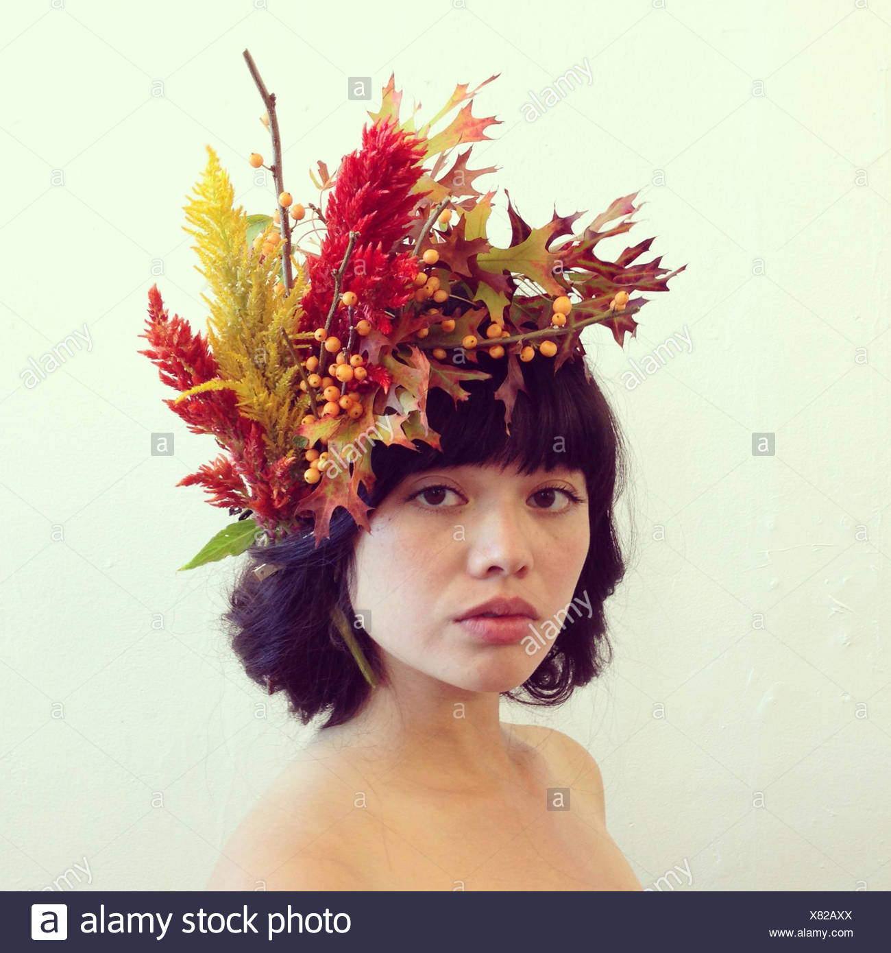 Portrait of a woman wearing a floral headdress - Stock Image