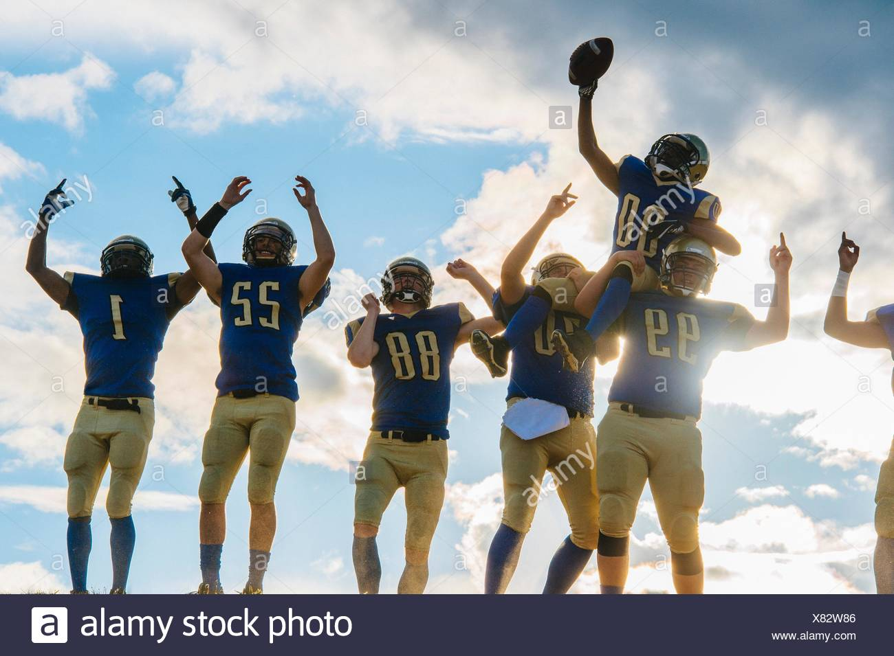 Group of young american football players, celebrating - Stock Image