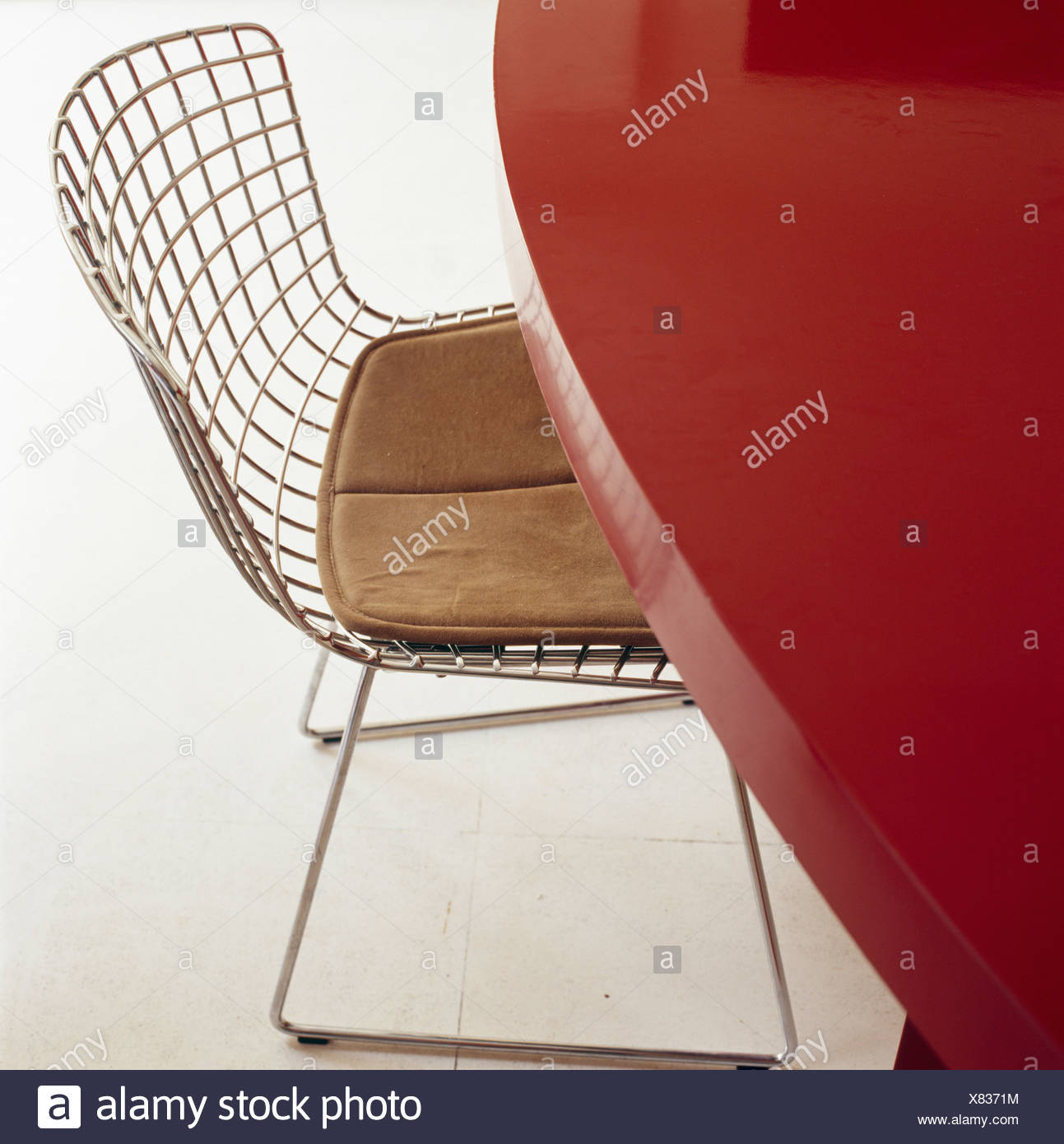 Close Up Of Charles Eames Wire Mesh Chair At Red Lacquered Table