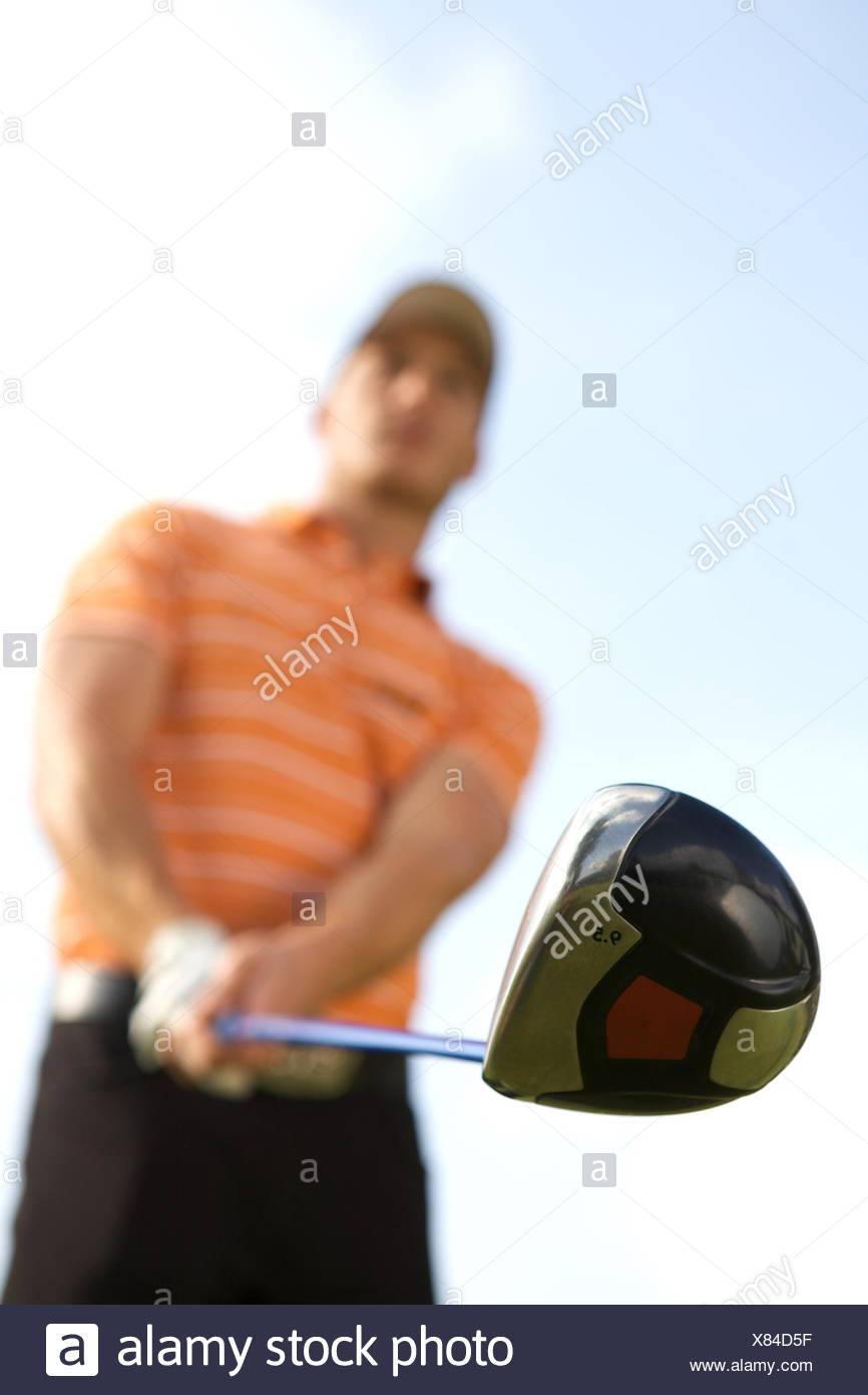 Young man playing golf, low angle view - Stock Image