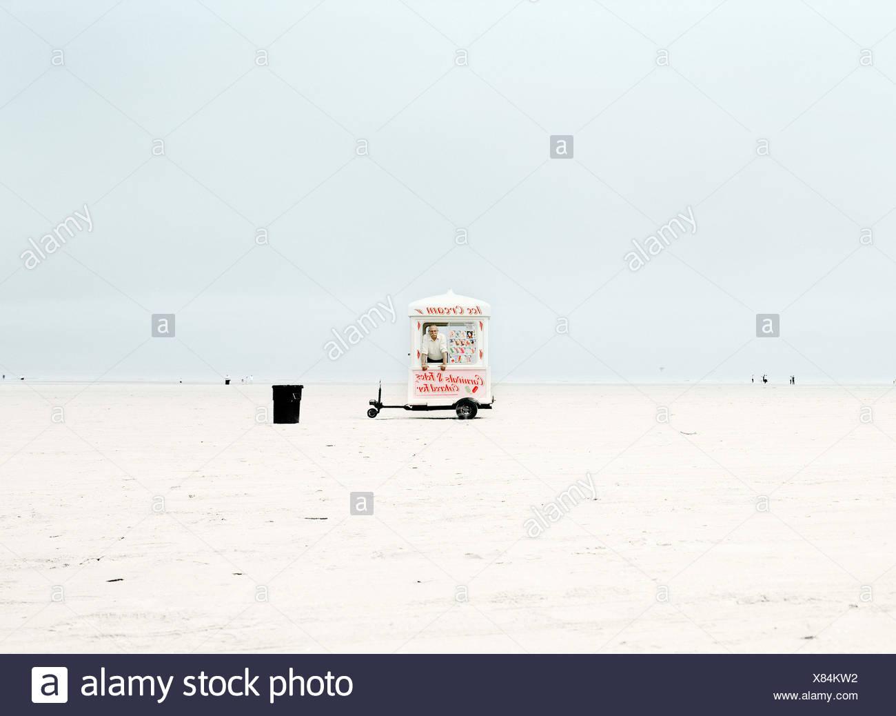 Man standing inside ice cream van on remote beach - Stock Image