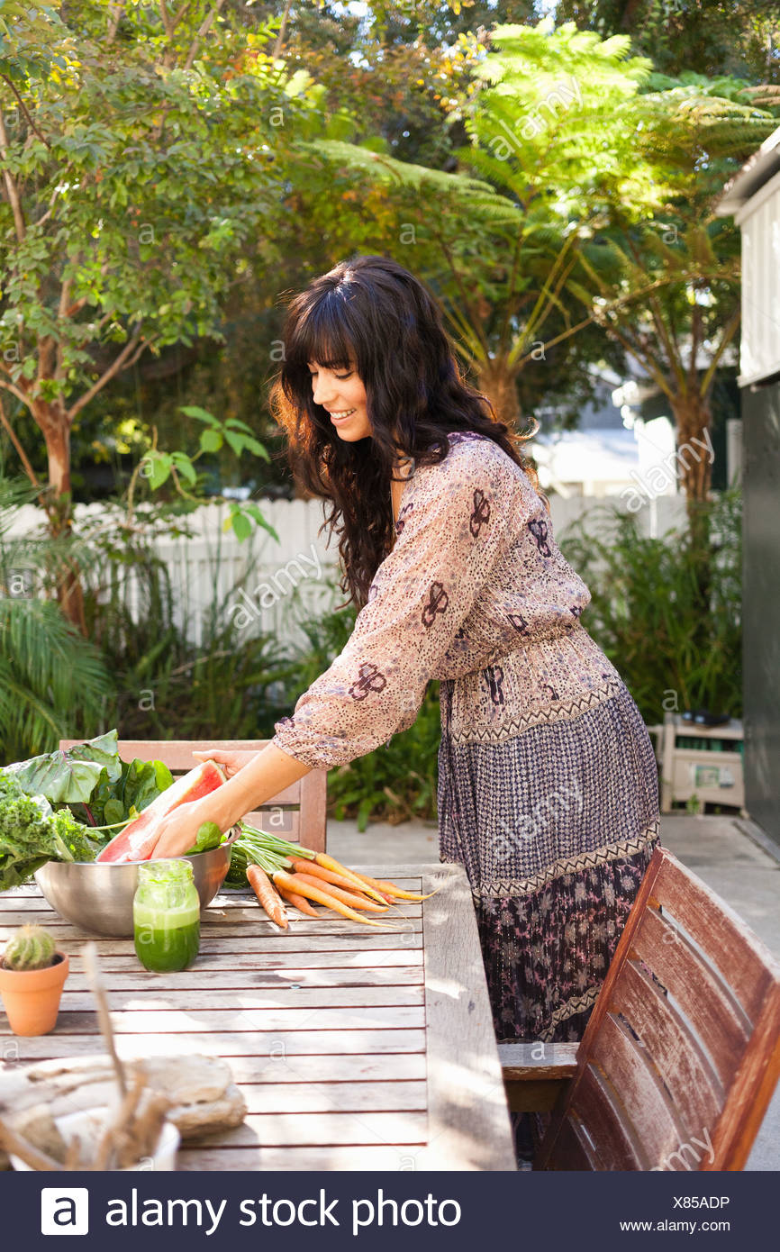 Young woman with vegetables on table - Stock Image