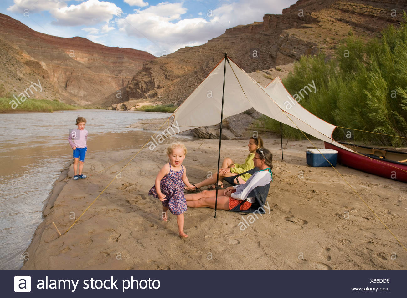 Two young girls playing near their mothers while camping on the San Juan River, Mexican Hat, Utah. - Stock Image